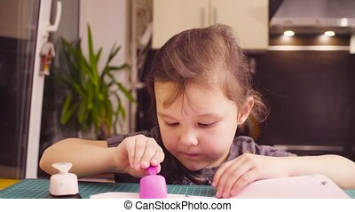 Little girl cutting flowers from white paper - Crane shot....