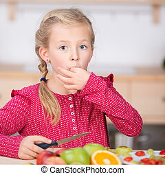 Little Girl Cutting Fruit In Kitchen