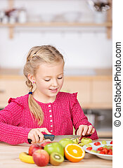Little Girl Cutting Fruit In the Kitchen