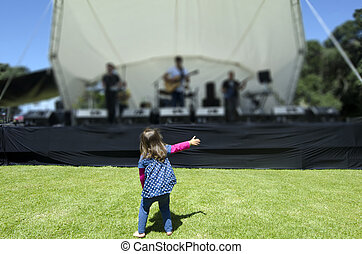 Little girl dances in a music concert