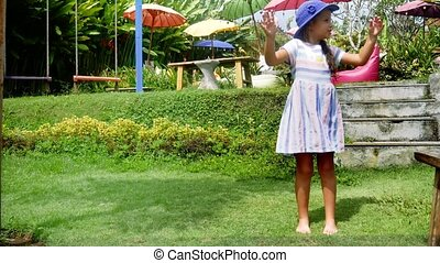 Little girl dancing in the garden and laughing