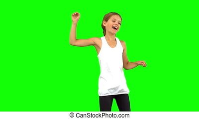Little girl dancing on green screen in slow motion