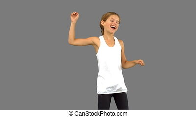 Little girl dancing on grey screen in slow motion