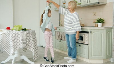 Little girl dancing with grandmother in kitchen, elderly woman showing thumbs-up