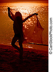 Little girl dancing with veil on the beach