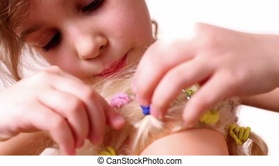 Little girl decorate dolls hairdo with bijouterie crystal,...