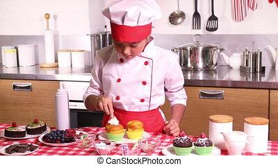 Little girl decorates muffin berry - Little girl in a chef ...