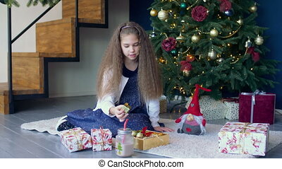 Little girl decorating christmas tree with toys - Cute...