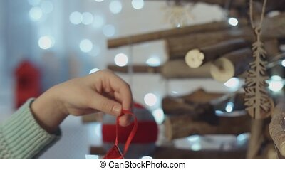 Little girl decorating wooden Christmas tree with toys