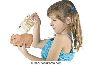 little girl depositing change in her piggy bank