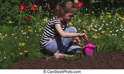 Little girl digging soil near flowers