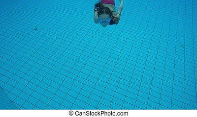 Little girl diving into swimming pool and swimming to the camera