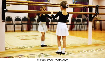 little girl does ballet leg movements while facing mirror in hall