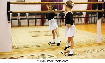 little girl does ballet leg movements while standing sideways to mirror at hall
