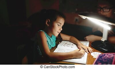 little girl does homework reads a book and writer at night....