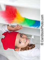 Little girl doing chores - dusting and cleaning with feather duster