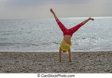 little girl doing exercise in the sandy beach by the sea