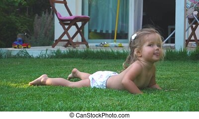 Little girl doing fitness exercises on lawn at backyard in...