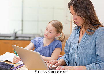 Little girl doing her homework while her mother is using notebook in a kitchen