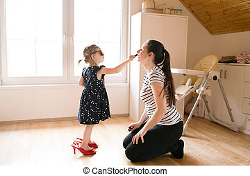 Little girl doing make-up to her attractive mother with...