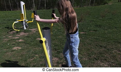 Little girl doing physical activities on stepping machine at outdoor