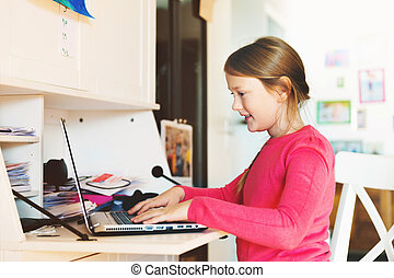 Little girl doing school homework with laptop pc