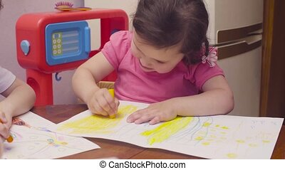 Little girl drawing at a table. Then she showing her picture