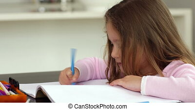 Little girl drawing at the kitchen table at home in kitchen
