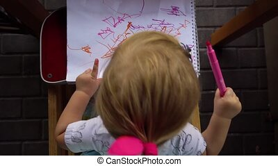 Little girl drawing in album. Top view - Little girl on...