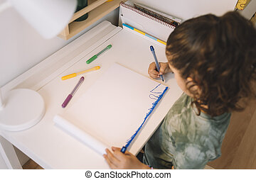 little girl drawing in her desk with color markers