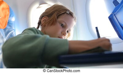 Little girl drawing in the airplane