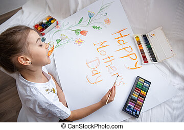 Little girl paints with paints and crayons greeting card for Mom on Mother's Day with the inscription Happy mother's day .