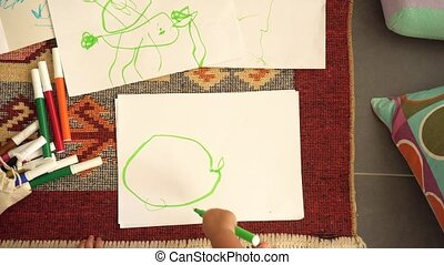 Little girl drawing on paper. View from top - Little girl...