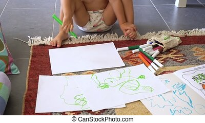 Little girl drawing on papers sitting in living room at home