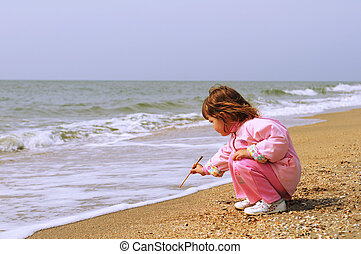 Little girl drawing on sand
