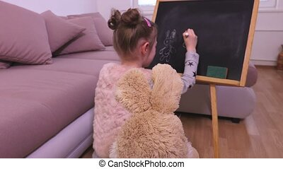Little girl drawing with chalk on a blackboard