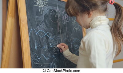Little girl drawing with chalk on board