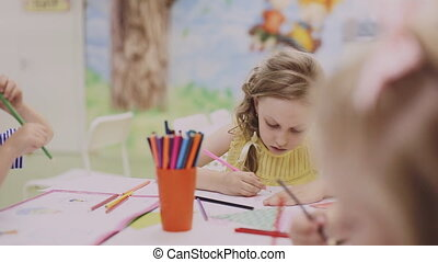 little girl drawing with colored pencils on paper