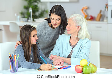 Little girl drawing with mother and grandma