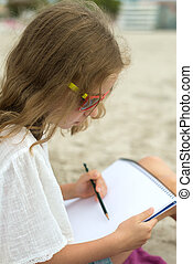 Little girl drawing with pencil on the beach.