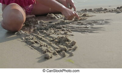 Little girl draws a figures in the sand on the beachbeaches
