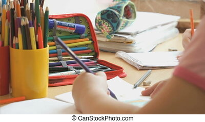 Little girl draws a pictures in the copybook
