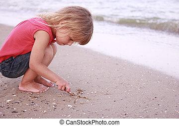Little girl draws a sun in the sand