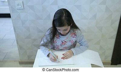 Little girl draws at the table