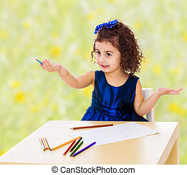 Little girl draws at the table with pencils