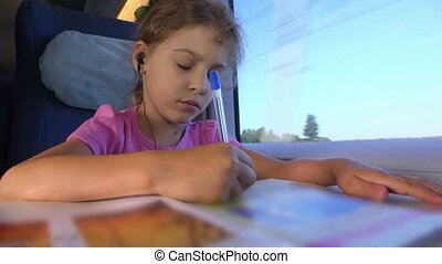 Little girl draws by pen in book when sits at train near window