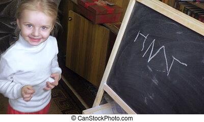 Little girl draws chalk on blackboard - On blackboard little...