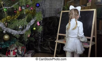 Little girl draws chalk on blackboard