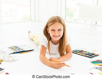 little girl draws lying on the floorlittle cheerful girl draws lying on the floor