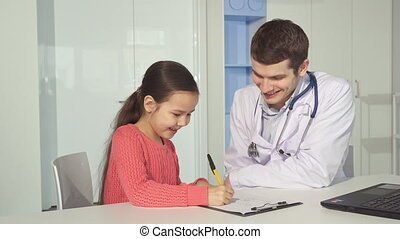Little girl draws on clipboard near the doctor
